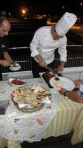 Chef offering up roasted pork at the Portuguese barbeque