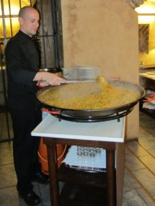 Chef preparing paella to serve 50 hungry travelers.