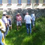 Looking at a commemorative plaque placed by the Eder River, Schwarzenau, Germany, the location of the first eight baptisms of the Church of the Brethren.